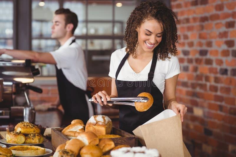 Lächelnde Kellnerin, die Brötchen in Papiertüte einsetzt lizenzfreie stockfotos