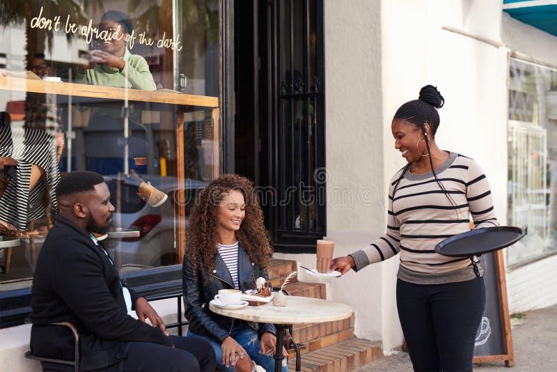 Lächelnde Kellnerin, die zwei junge Freunde an einem Straßencafé dient stockfoto