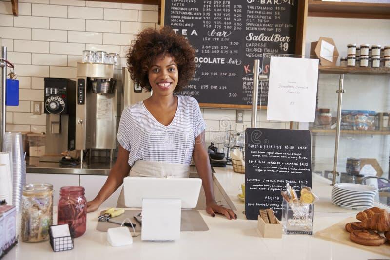 Lächelnde Kellnerin hinter Zähler an einer Kaffeestube, Abschluss oben lizenzfreie stockbilder