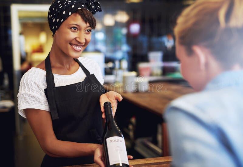Lächelnde Kellnerin oder Barmixer, die Rotwein zeigen lizenzfreie stockfotografie