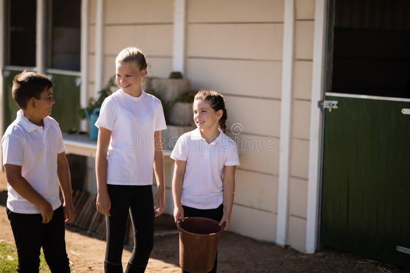 Lächelnde Kinder, die außerhalb des Stalles sprechen stockbilder