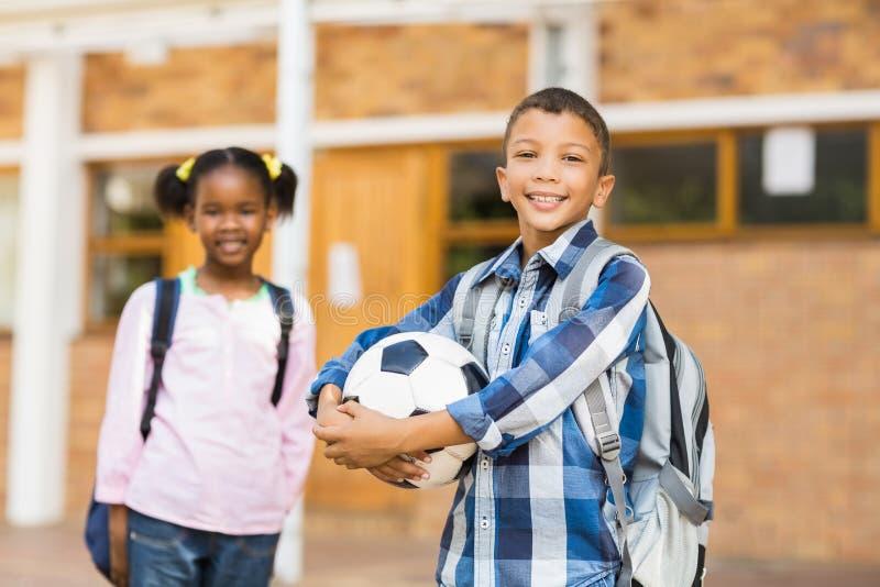 Lächelnde Kinder, die in der Schule im Klassenzimmer stehen stockbilder