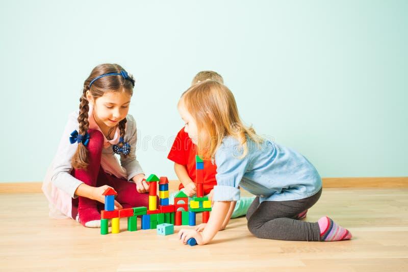 Lächelnde Kinder, die Gebäude von den bunten Blöcken spielen lizenzfreie stockbilder
