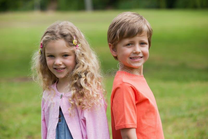 Lächelnde Kinder, die am Park stehen stockbilder