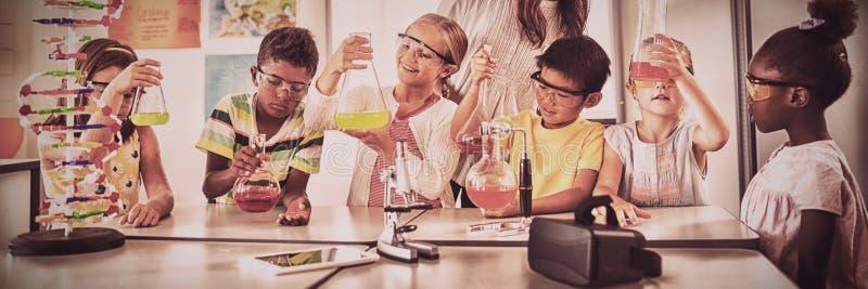 Lächelnde Kinder, die Wissenschaftsprojekt tun stockfotografie