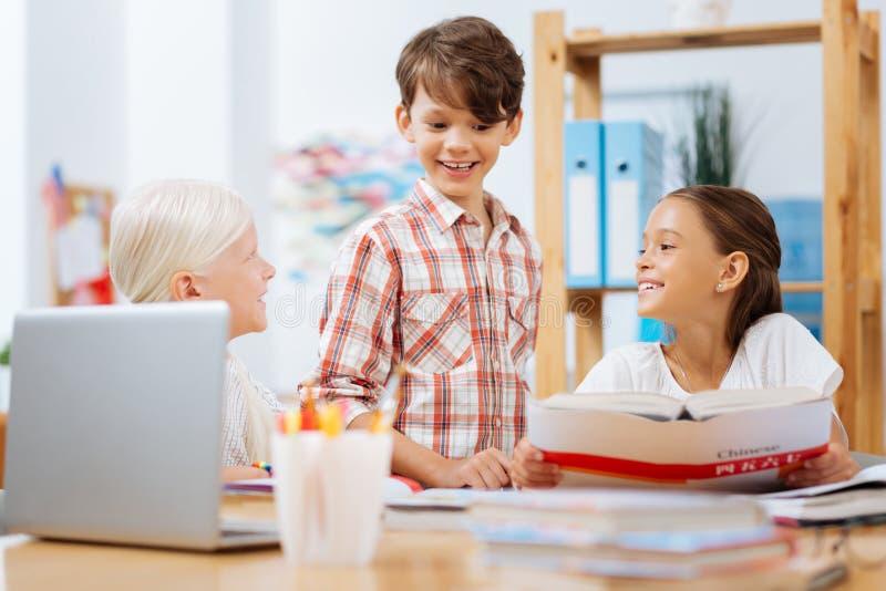 Lächelnde Kinder, die zusammen Hausarbeit in einem Raum tun lizenzfreies stockfoto
