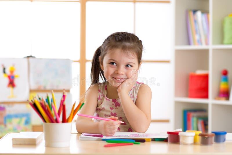 Lächelnde Kindermädchenzeichnung mit Farbe zeichnet in Kindertagesstätte an lizenzfreie stockfotografie