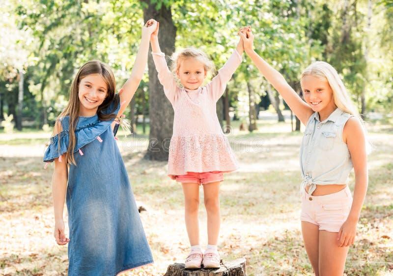 Lächelnde kleine Mädchen stehen mit den froh angehobenen Händen im Park stockbild