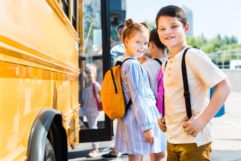 lächelnde kleine Schüler, die Schulbus betreten stockfotografie