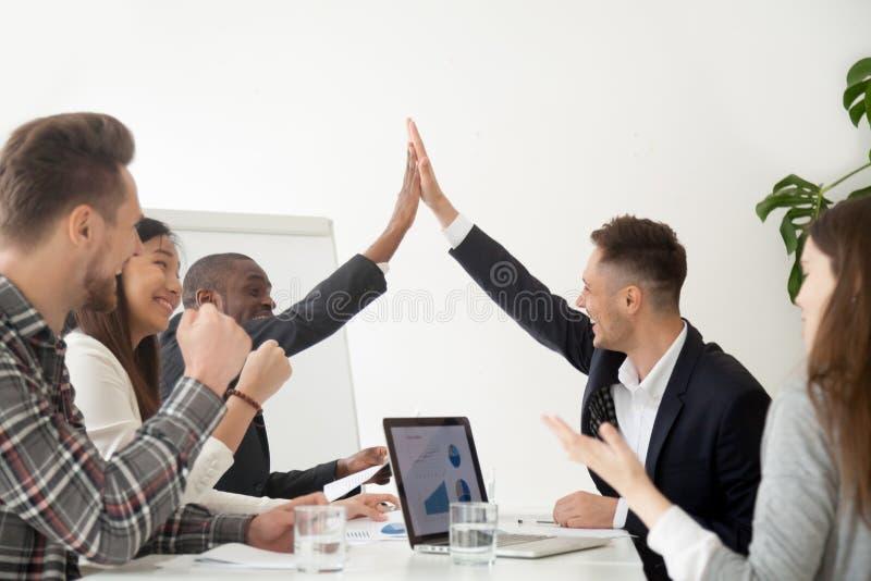 Lächelnde Kollegen, die das Hoch fünf aufgeregt durch Geschäftsergebnisse geben stockfoto