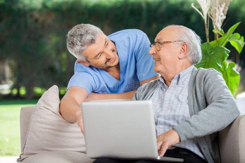 Lächelnde Krankenschwester Assisting Senior Man, wenn Laptop verwendet wird lizenzfreies stockbild