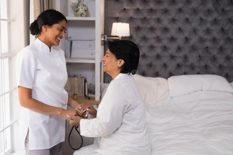 Lächelnde Krankenschwester, die reife Frau auf Bett tröstet lizenzfreies stockbild