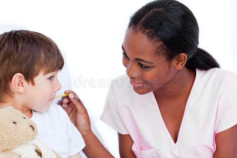 Lächelnde Krankenschwester, die Temperatur des kleinen Jungen nimmt stockfotografie