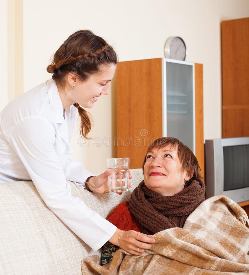 Lächelnde Krankenschwester im einheitlichen Interessieren für reifes woma lizenzfreies stockbild