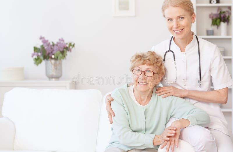 Lächelnde Krankenschwester sitzt mit älterer Frau stockbild