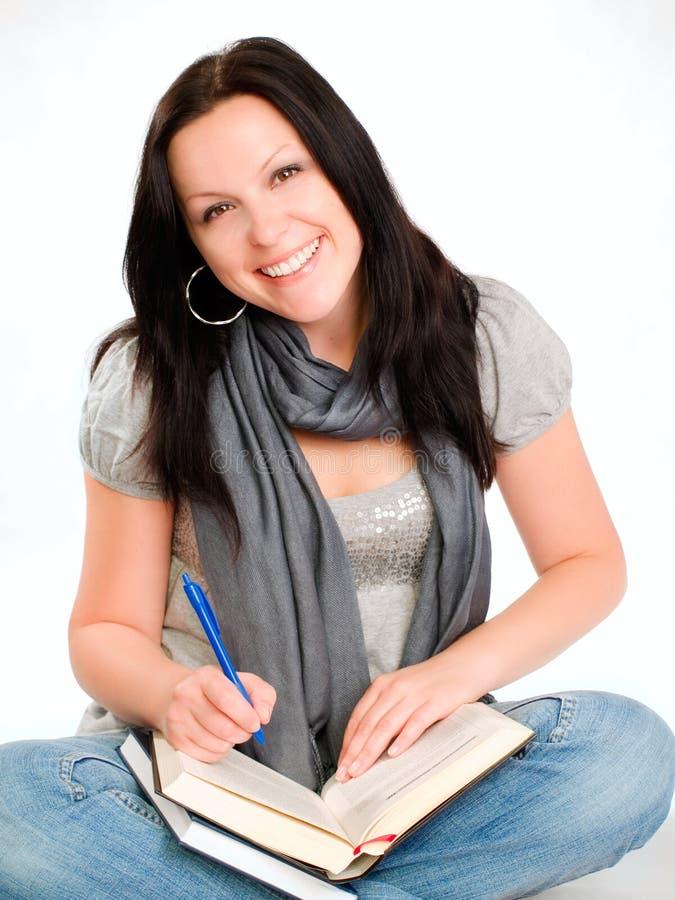 Lächelnde Kursteilnehmerfrau, die innen Anmerkungen bildet lizenzfreie stockfotos