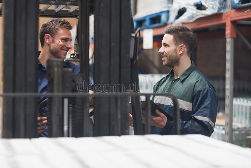 Lächelnde Lagerarbeitskräfte, die zusammen sprechen lizenzfreie stockfotos