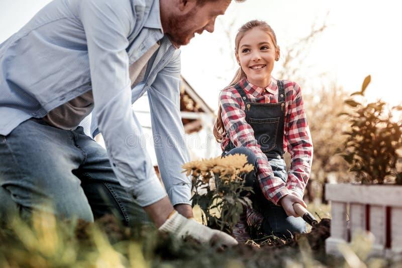 Lächelnde langhaarige Tochter, die seinem erstaunlichen Vater hilft stockbilder
