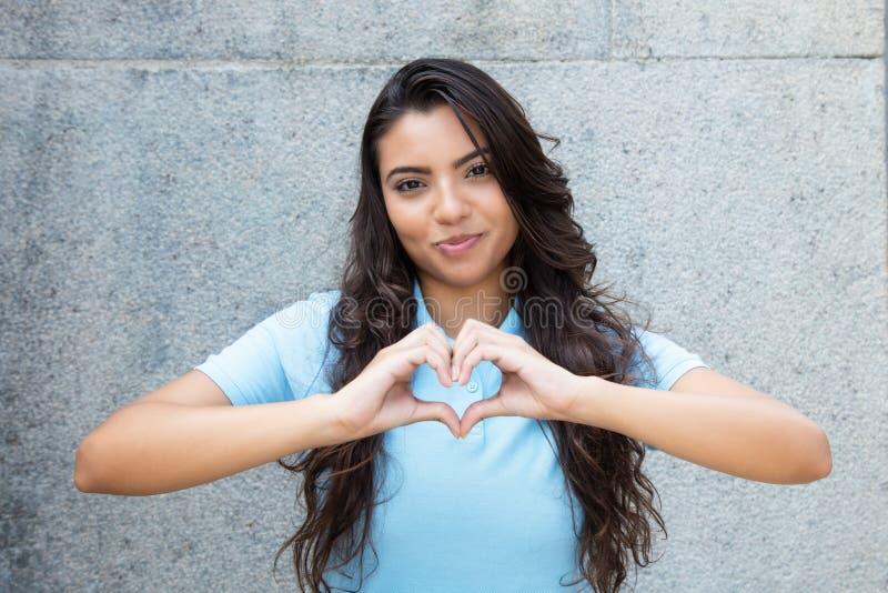 Lächelnde lateinamerikanische verliebte Frau, die Herz mit den Händen zeigt stockfotografie