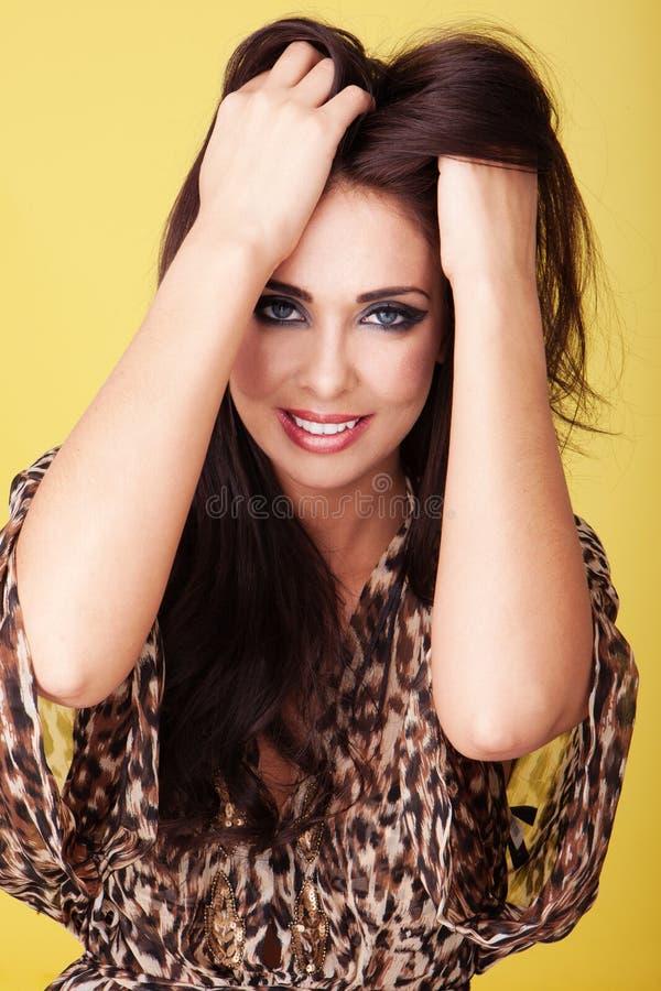 Lächelnde laufende Hände der Frau durch ihr Haar lizenzfreies stockbild