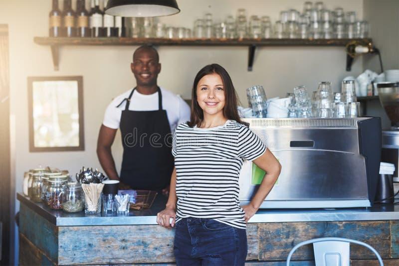 Lächelnde Lebensmittelservice-Arbeitskräfte im Kaffeehaus lizenzfreie stockfotografie