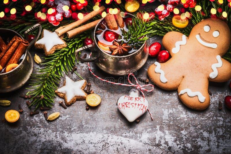Lächelnde Lebkuchenmänner mit Becher Glühwein, Weihnachtsdekoration und Feiertagsplätzchen und -gewürzen auf dunklen rustikalen H lizenzfreies stockbild