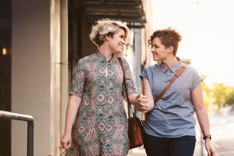 Lächelnde lesbische Paare, die mit Einkaufstaschen in der Stadt gehen stockbilder