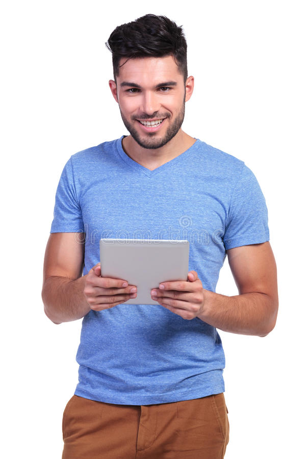 Lächelnde Lesung des jungen Mannes auf einer Tablettenauflage lizenzfreies stockfoto