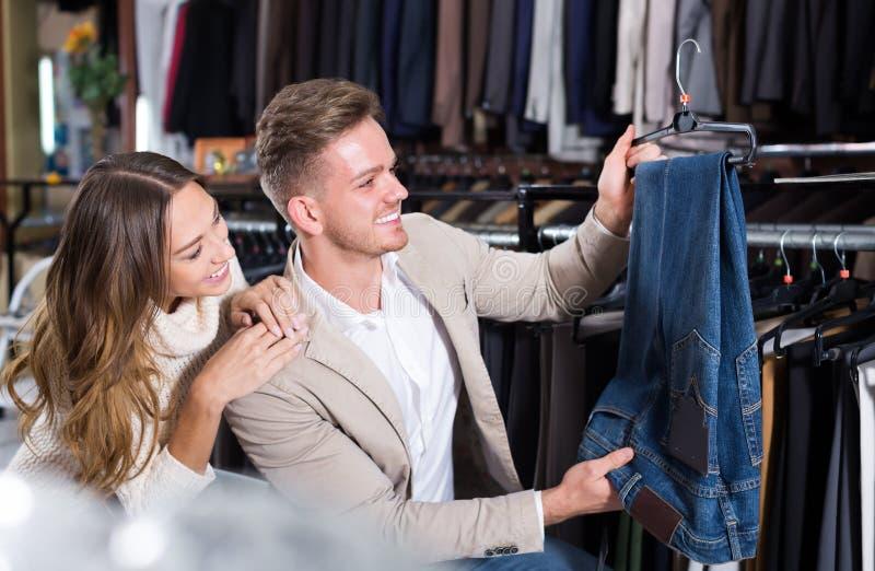 Lächelnde liebevolle Paare, die auf neuer Hose entscheiden stockfoto