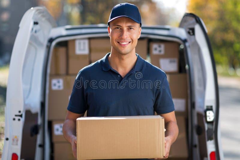 Lächelnde Liefererstellung vor seinem Packwagen, der ein Paket hält stockfotografie