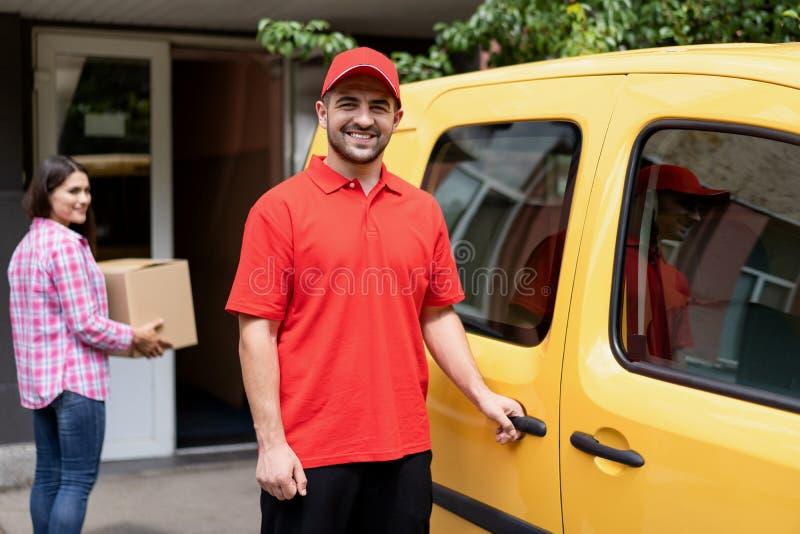 Lächelnde Lieferungskerlstellung nahe gelbem Packwagen stockfotos