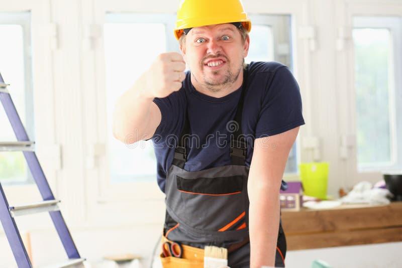 Lächelnde lustige Arbeitskraft im gelben Sturzhelm stockfotografie