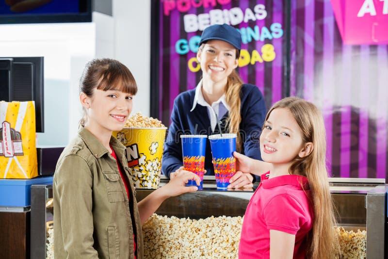 Lächelnde Mädchen, die Popcorn und Getränke von kaufen stockfotografie