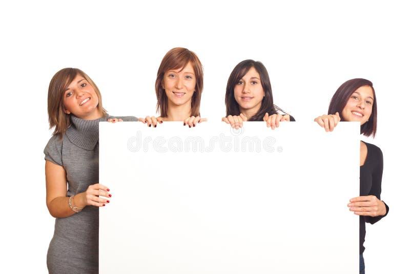 Lächelnde Mädchen halten unbelegte Anschlagtafel an lizenzfreie stockbilder