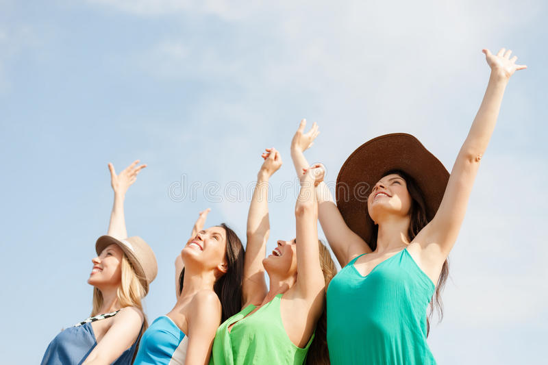 Lächelnde Mädchen mit den Händen oben auf dem Strand lizenzfreies stockfoto