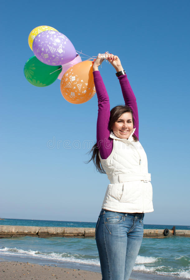 Lächelnde Mädchenholdingballone lizenzfreie stockfotos