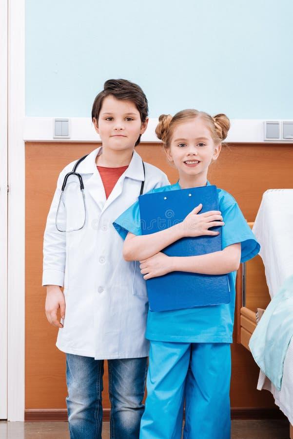 Lächelnde Mädchenkrankenschwester mit hörendem Herzschlag des Stethoskops des Jungen stockfotografie