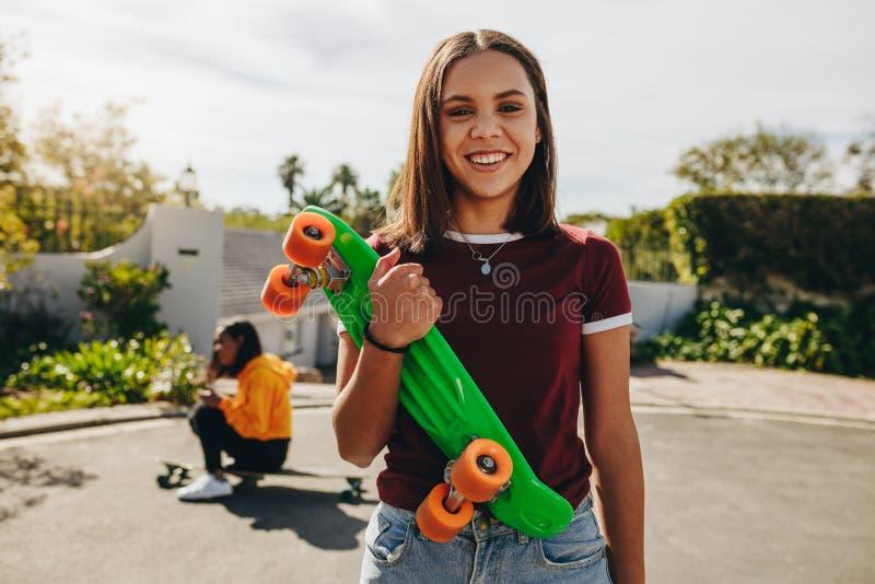 Lächelnde Mädchenstellung auf der Straße, die ein Skateboard hält lizenzfreie stockbilder