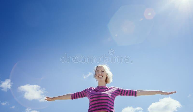 Lächelnde Mädchenverbreitungsarme in Form eines Flugzeuges Der lowr Winkel: die Ansicht von unterhalb lizenzfreie stockfotografie