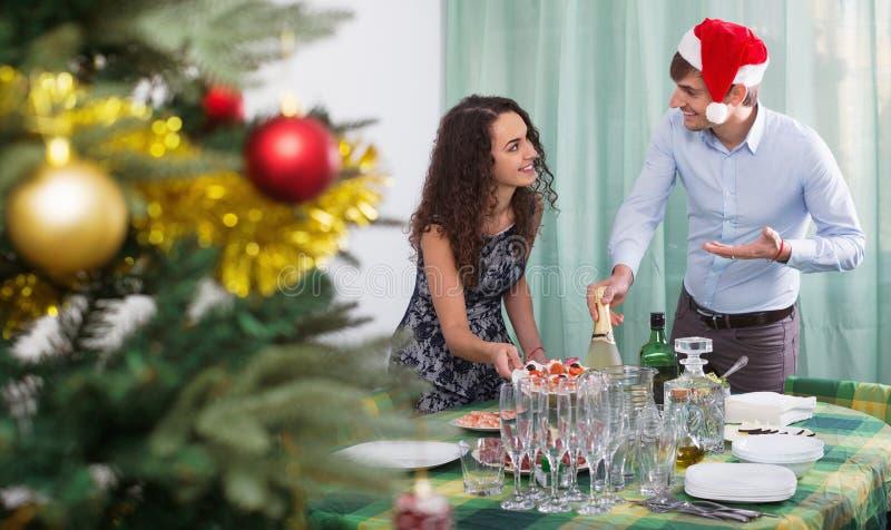 Lächelnde Mann- und Mädchenumhüllung Weihnachtstabelle für Gäste lizenzfreies stockfoto