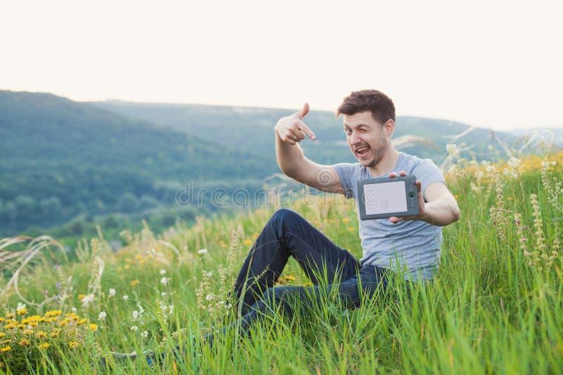Lächelnde Mann Winks und halten ein eBook lizenzfreie stockfotografie
