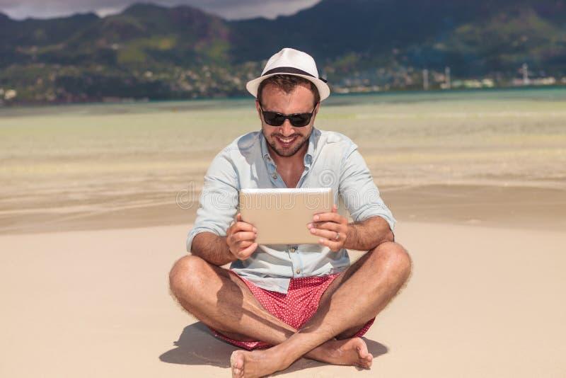 Lächelnde Mannlesung auf Tablette beim den Strand sich hinsetzen stockbild