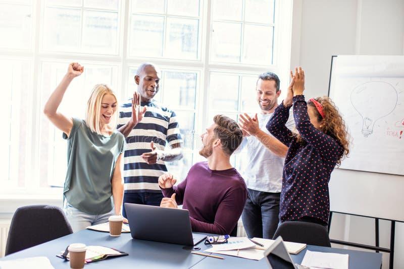 Lächelnde Mitarbeiter, die zusammen während einer Bürositzung zujubeln lizenzfreies stockfoto