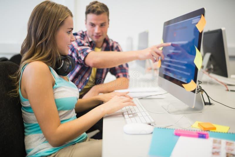 Lächelnde Mitschüler, die zusammen eine Aufgabe im Computerraum tun stockbild