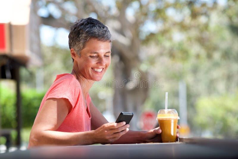 Lächelnde Mittelalterfrau, die draußen mit Handy und Getränk sitzt stockfotografie
