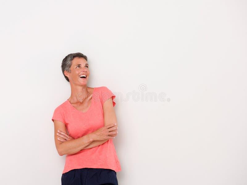 Lächelnde Mittelalterfrau gegen weiße Wand stockbild