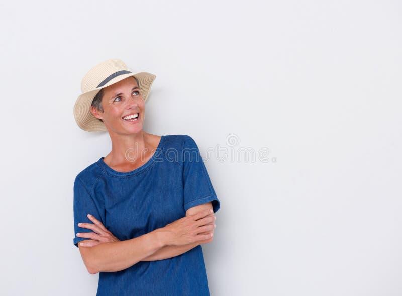 Lächelnde Mittelalterfrau gegen weiße Wand mit Hut lizenzfreies stockfoto