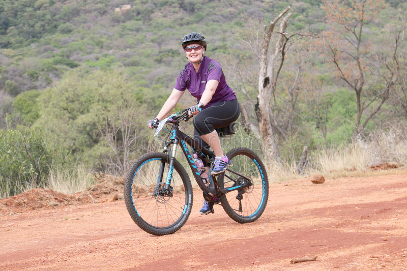 Lächelnde mittlere Greisin, die draußen Fahrt am Berg Bik genießt stockfotografie