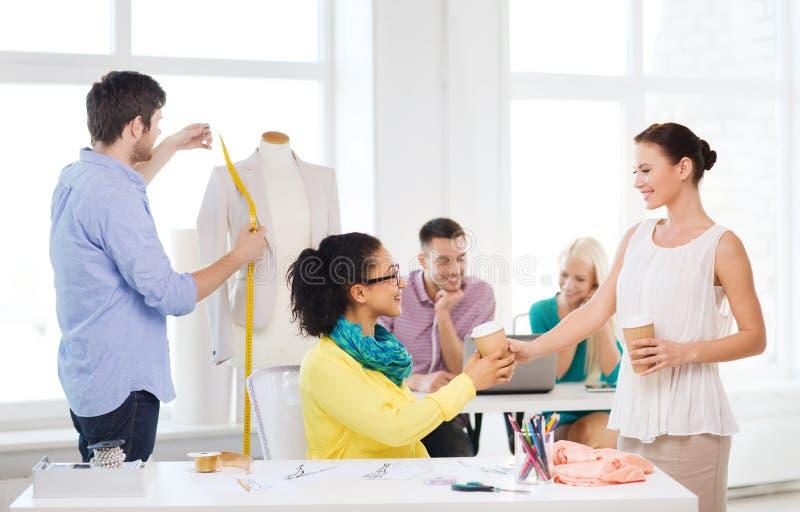 Lächelnde Modedesigner, die im Büro arbeiten lizenzfreies stockbild