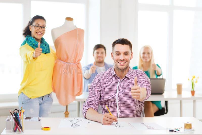 Lächelnde Modedesigner, die im Büro arbeiten stockbild